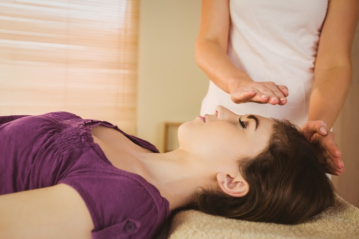 Bigstock- 79287707 - Young woman having a reiki treatment in therapy room